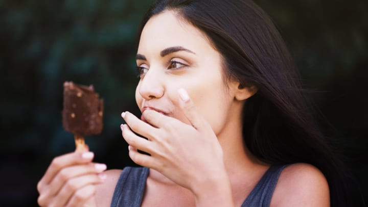 Close-up of hand holding chocolate-covered ice cream bar on popsicle stick