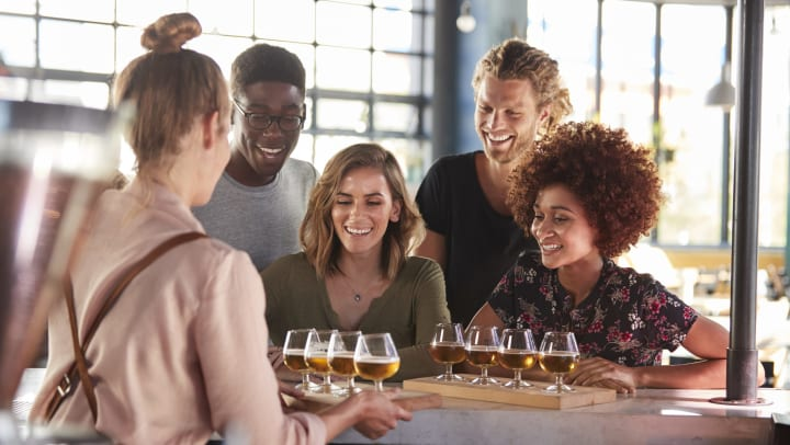 Woman serving beer tasters to a group of people smiling.