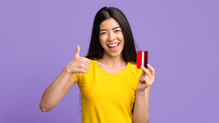 Smiling woman showing thumbs up, holding credit card