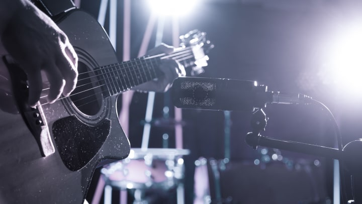 Closeup of microphone recording an acoustic guitar in a recording studio or concert hall, with a drum set in the background out of focus.