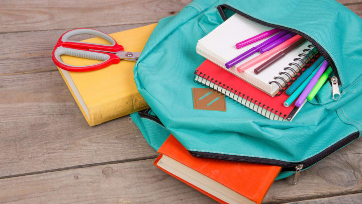 A light blue backpack on its side with a bunch of supplies falling out including notebooks, scissors, books, and colored markers.