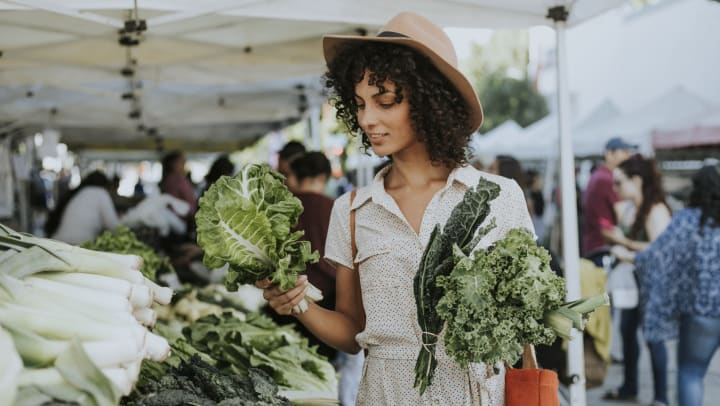 A woman at a farmers market holding produce