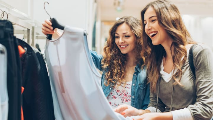 Two ladies looking at a light blue sleeveless shirt and smiling while shopping in a clothing store.