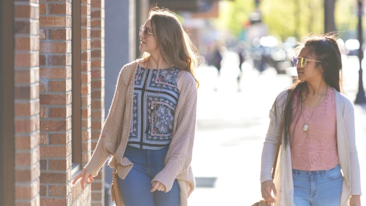 Two young women wearing sunglasses, jeans, tops, and light sweaters, walking and window shopping