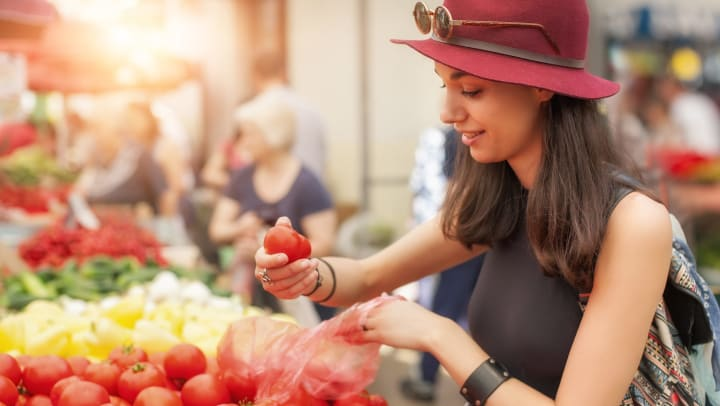 A young woman buying fruit and vegetables at a weekly market.