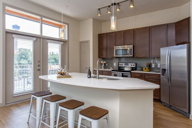 Kitchen with an island in a model home at Agave in San Antonio, Texas