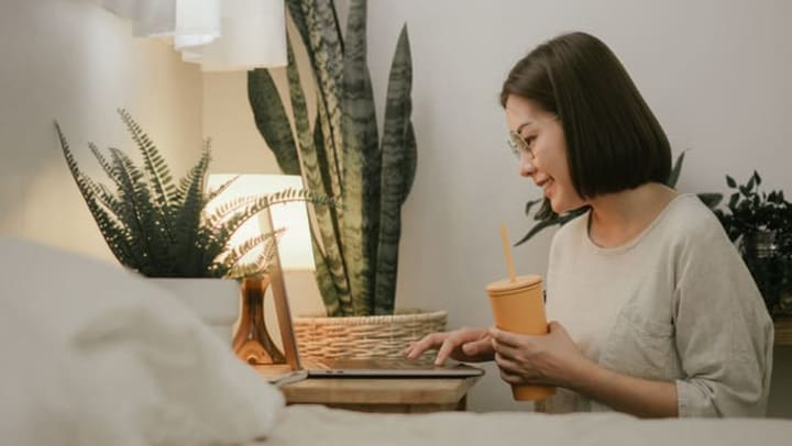 A smiling woman is looking at her laptop and holding a cup, surrounded by plants.