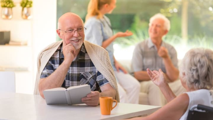 Residents having a conversation while reading and drinking coffee