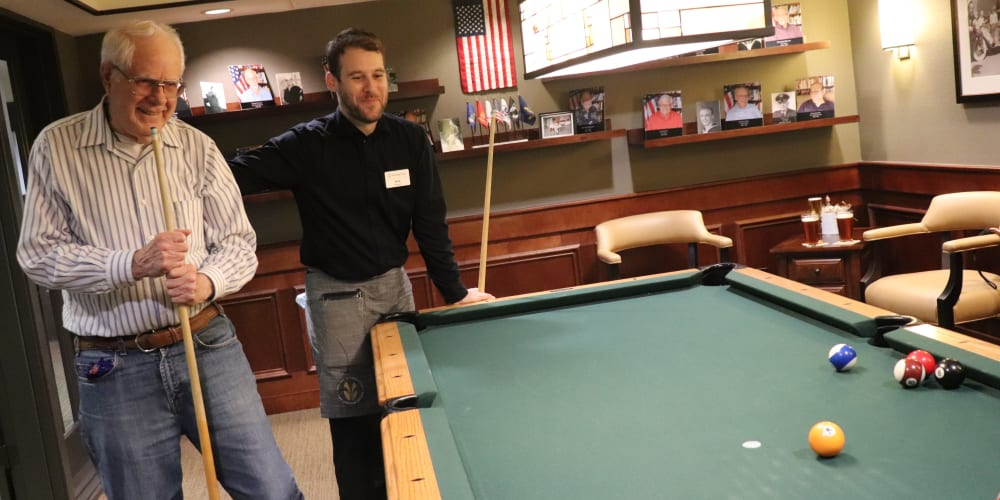 Resident playing pool with server at The Springs at Carman Oaks in Lake Oswego, Oregon.