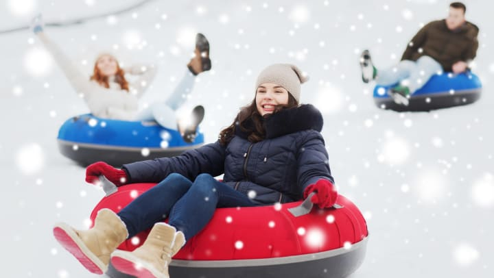 Two young women and a young man slide down a snowy hill on inflatable tubes.