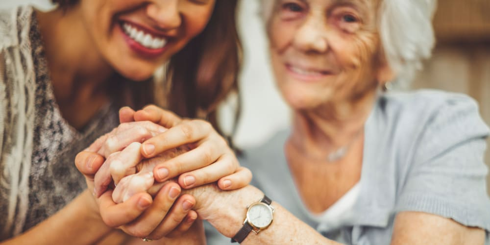A family member holding a resident's hand at Mission Healthcare at Bellevue in Bellevue, Washington.