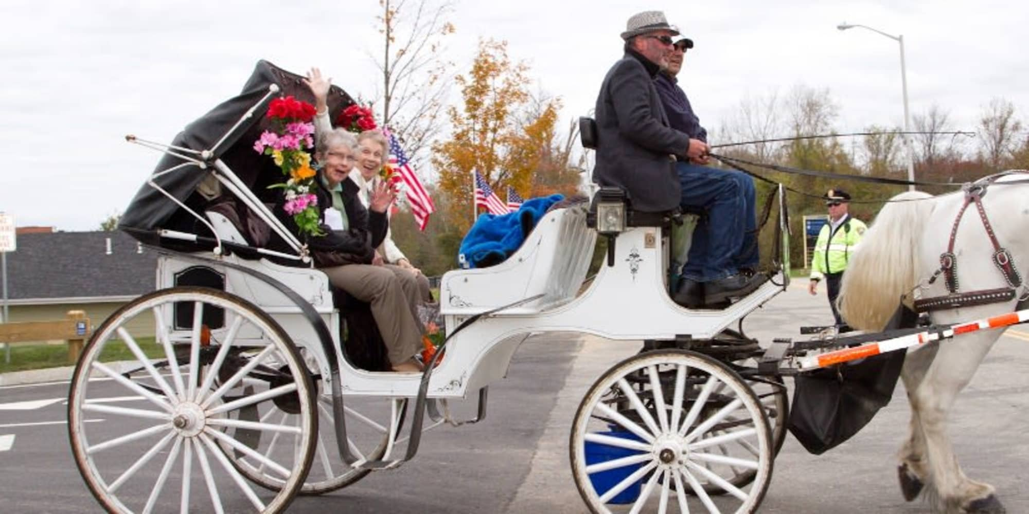Two residents from Alexis Estates Gracious Retirement Living in Allen, Texas, in a horse-drawn carriage