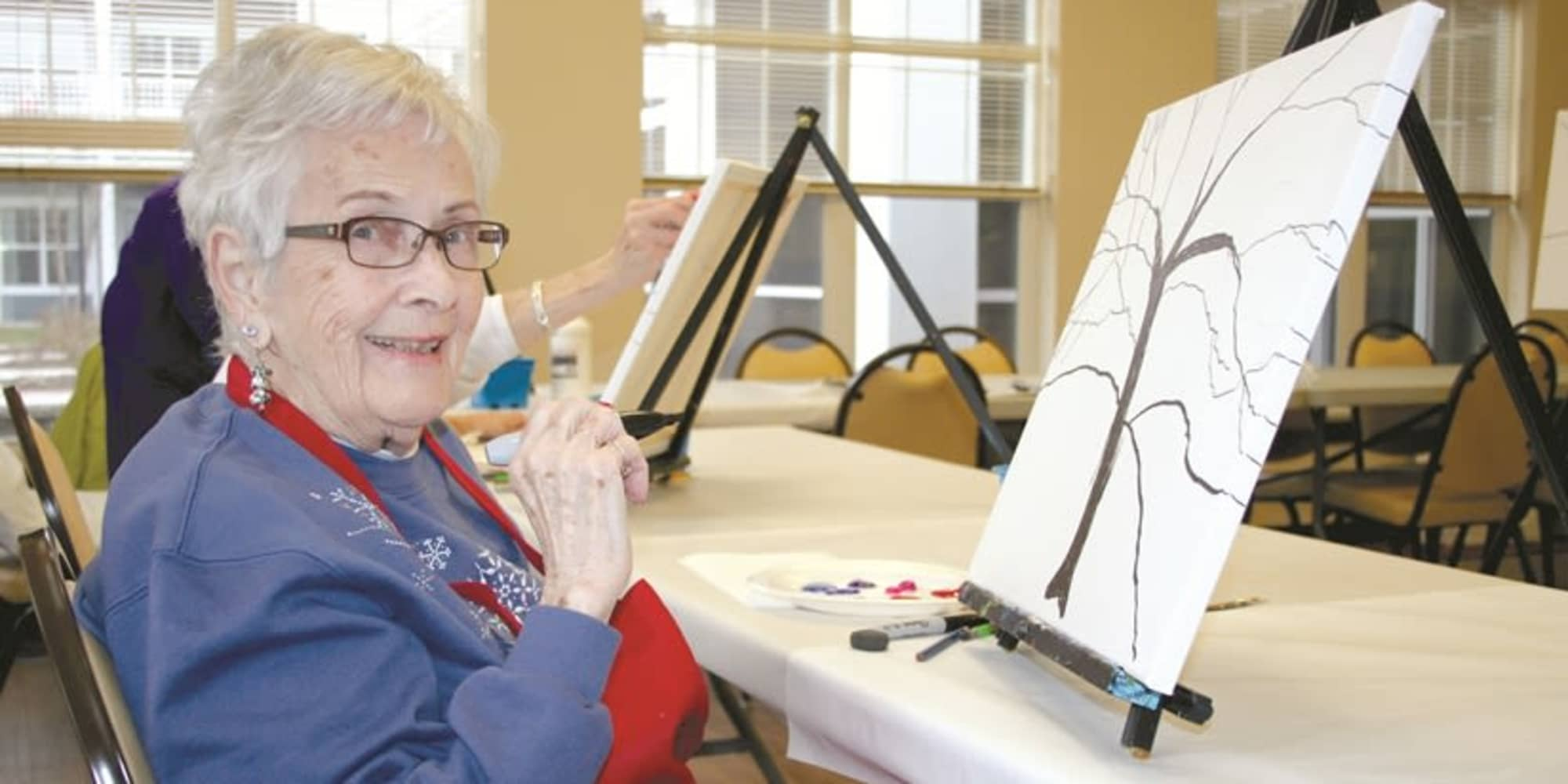 A resident from Fairview Estates Gracious Retirement Living in Hopkinton, Massachusetts painting a tree