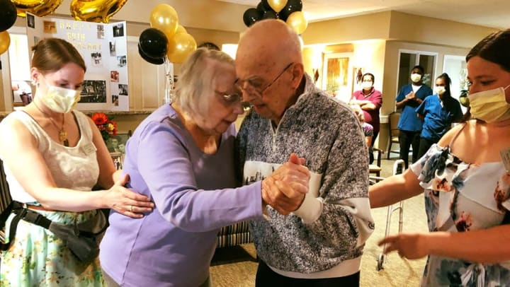 elderly couple dancing together with support from caregivers