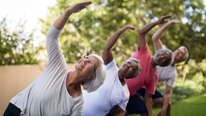 Active seniors doing yoga outside