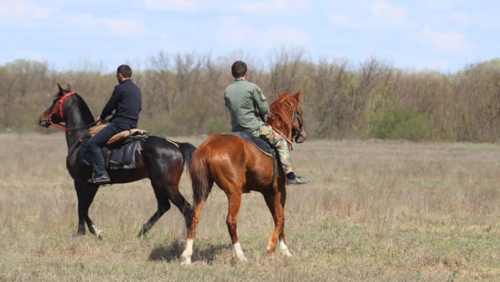 Two residents enjoying a horseback ride near Olympus Willow Park in Willow Park, Texas.
