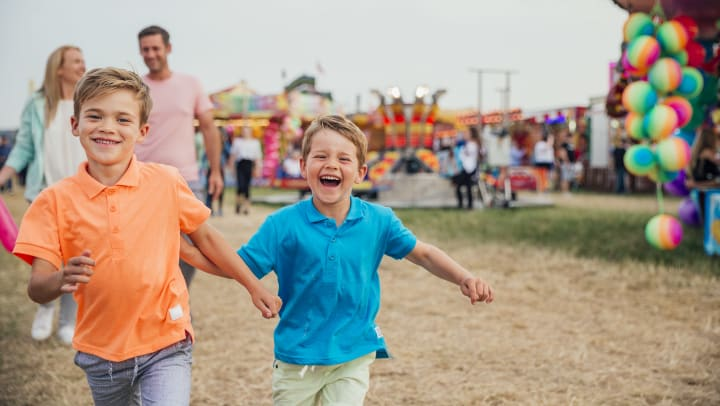 Two kids running and smiling at the fair