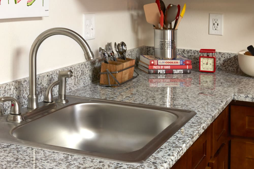 Renovated Kitchen at Trifecta Apartments Featuring Granite and New Stainless Sink