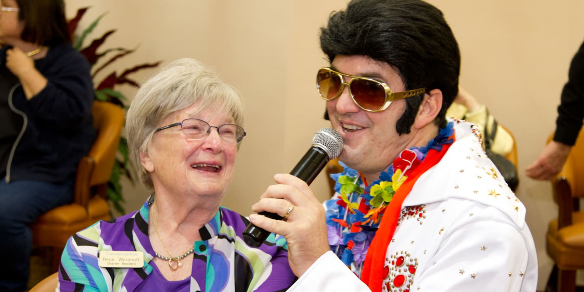 A happy resident from Colonial Gardens Gracious Retirement Living in Beverly, Massachusetts listening to an Elvis impersonator sing