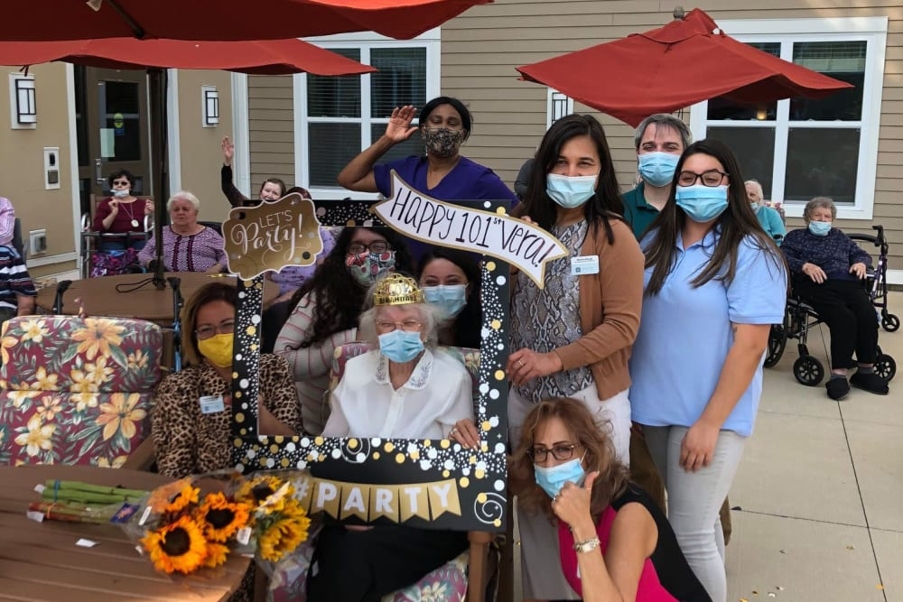 Resident and masked caretakers celebrating outside at Anthology Senior Living in Denver, Colorado