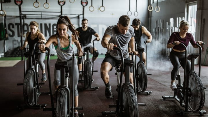 A group of 6 people pedal on a stationary assault bike in a CrossFit gym