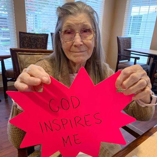 Resident Holding a piece of paper depicting the text 'God inspires me' at Oxford Glen Memory Care at Sachse in Sachse, Texas