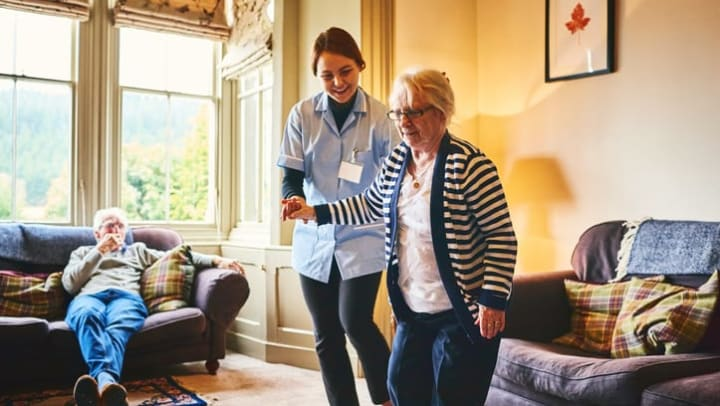 Nurse supports a senior woman as she walks indoors at Brightwater Senior Living