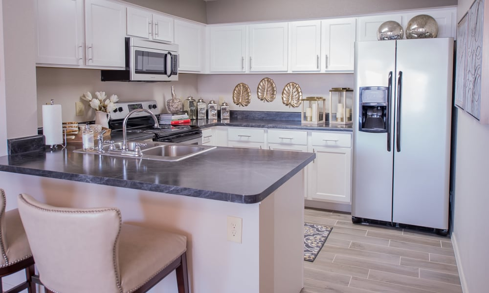 Kitchen with stainless steel appliances at Cottages at Tallgrass Point Apartments in Owasso, Oklahoma