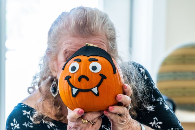 A resident poses with a pumpkin craft at Harmony at West Ashley in Charleston, South Carolina