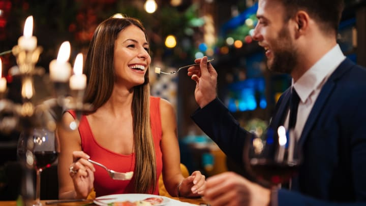 A smiling couple enjoy a romantic dinner in a restaurant.