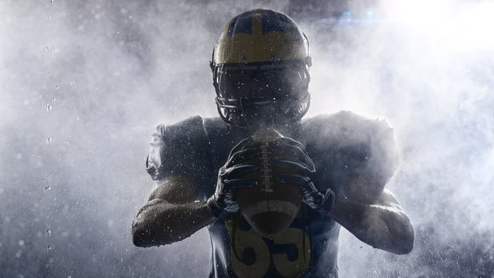 A football player in shadow and smoke holding a football between his hands.