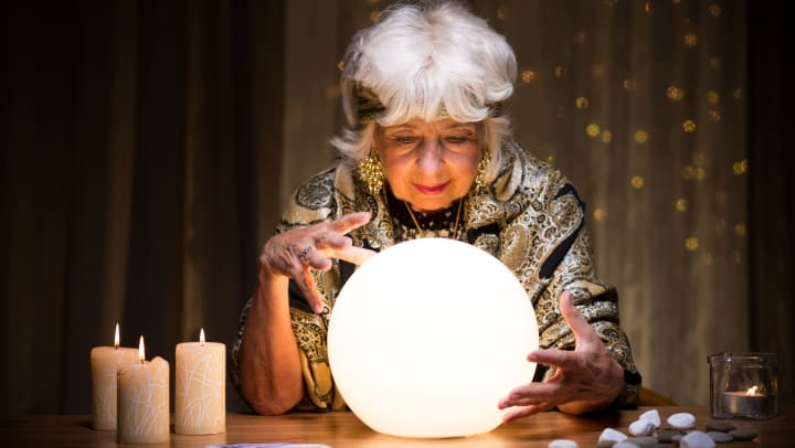 Senior woman dressed as fortune teller for Halloween looks into crystal ball.