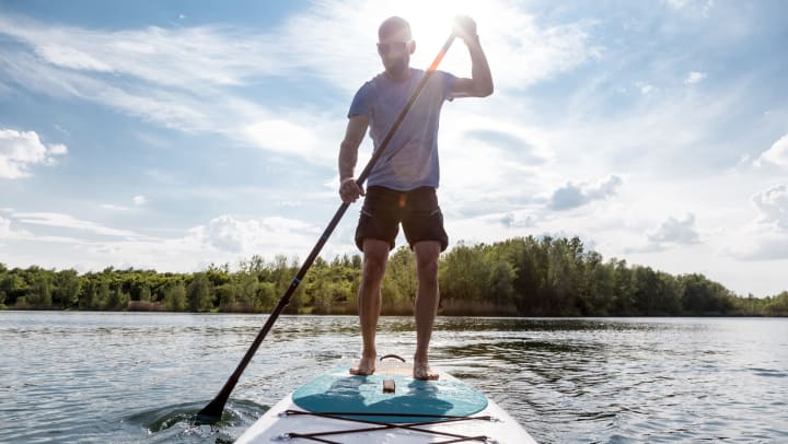 A man stand up paddle boarding in Jacksonville, Florida near Cape House