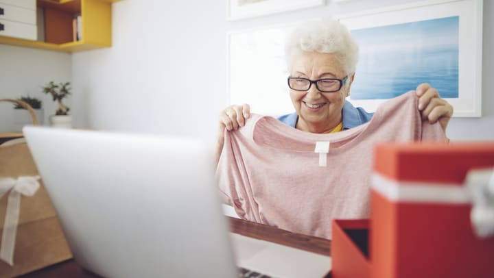 Senior woman holding up a shirt and smiling with an open box and open laptop computer in the foreground.