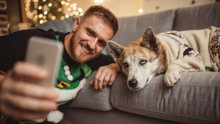 Man wearing ugly Christmas sweater taking a selfie with his dog