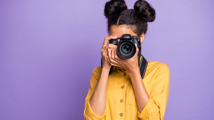 Woman in yellow shirt holding a camera up to her face on a purple background.