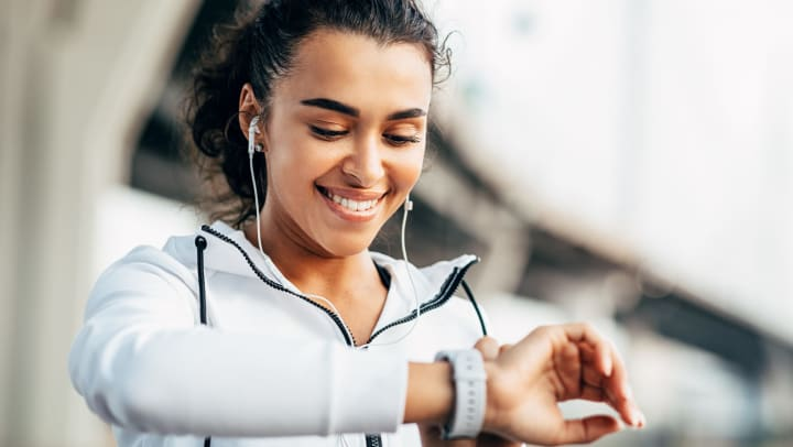 Smiling young woman wearing headphones and a light jacket looking at the face of her wristwatch