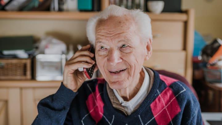 Elderly man on the phone smiling.