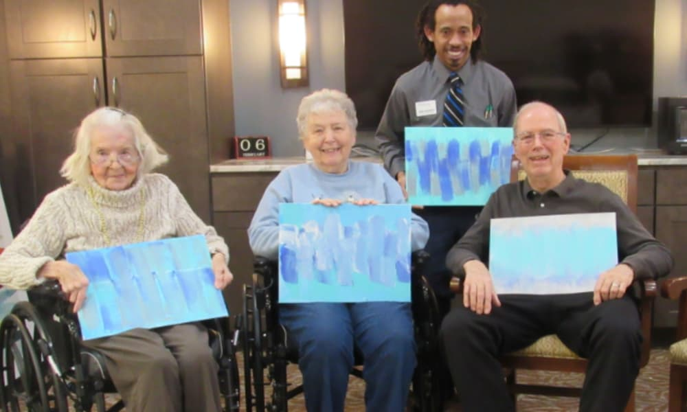 three senior residents and staff holding up their paintings