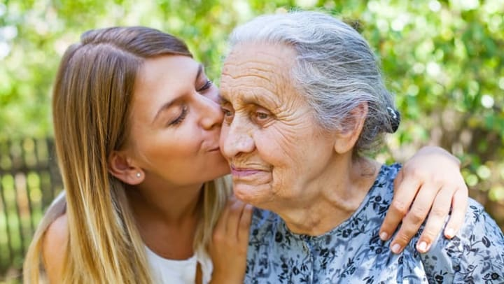 Younger woman kissing her mother on the cheek in a park setting near {{location_name}} in {{location_city}}, {{location_state_name}}