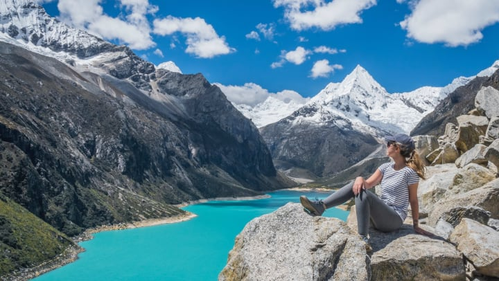 Picture of a woman sitting on a boulder overlooking a glacier-fed lake with snow-covered mountains in the background
