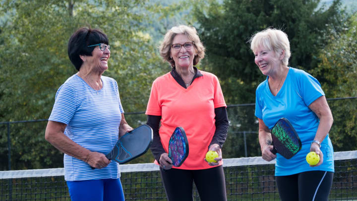 Three women holding tennis rackets.
