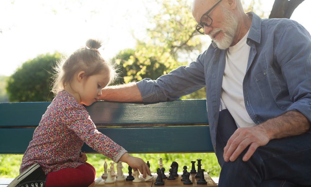 A resident and a small child playing chess at Touchmark in the West Hills in Portland, Oregon