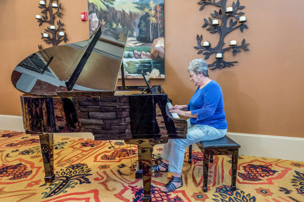 A resident playing piano at Watercrest at Kingwood in Kingwood, Texas