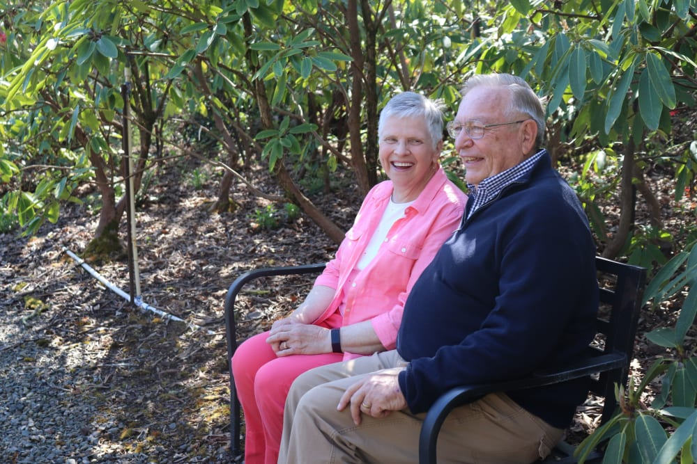 Two residents sitting in the gardens at The Springs at Greer Gardens in Eugene, Oregon.