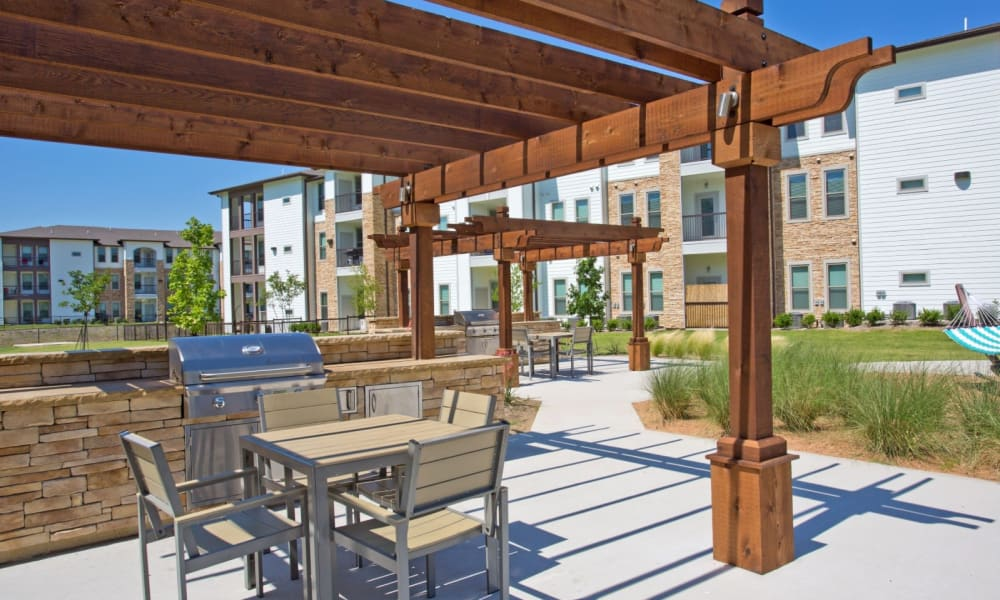 Grilling area with tables and chairs near the pool at Bellrock Upper North in Haltom City, Texas