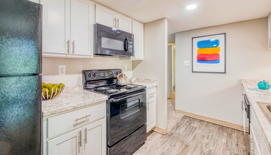 Modern kitchen with white cabinets in a model home at Preserve at Cradlerock Apartment Homes in Columbia, Maryland