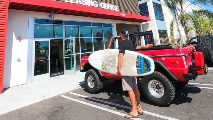 Man holding a surfboard stands next to a red jeep outside a self storage facility