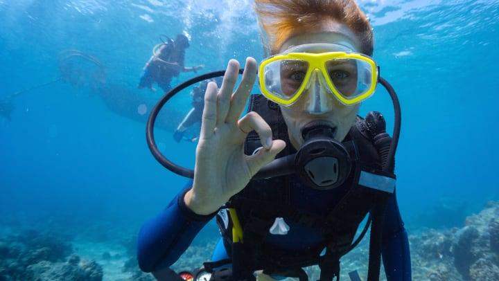 Woman underwater with scuba gear on.