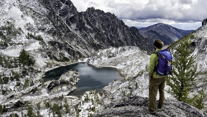 Man standing on a granite rock mountain pass looking down at a small lake and rugged mountain peaks